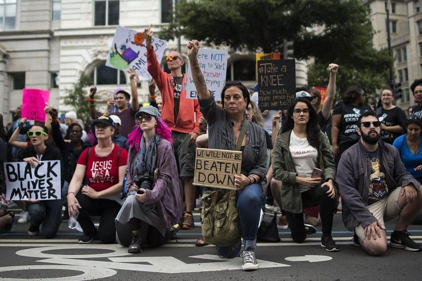 Protesters take a knee near the Trump hotel as they take part in the march for Racial Justice in Washington, on Sept 30, 2017.