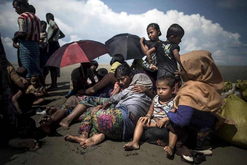 Rohingya Muslim refugees rest upon arrival on the Bangladeshi shoreline of the Naf river after crossing the border from Myanmar in Teknaf on Sept 30, 2017.