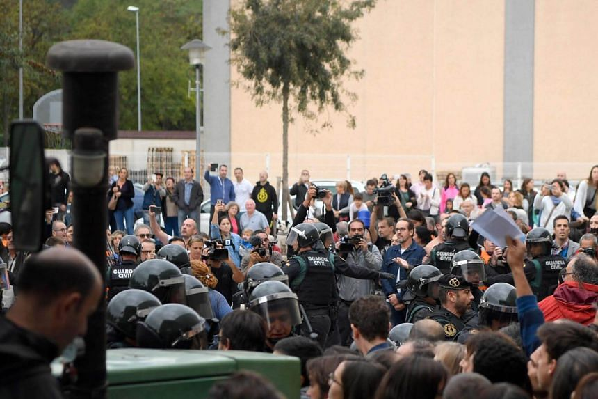 According to a witnes, riot police clashed with voters outside a Barcelona voting station, where dozens of police used riot shields to push people back.