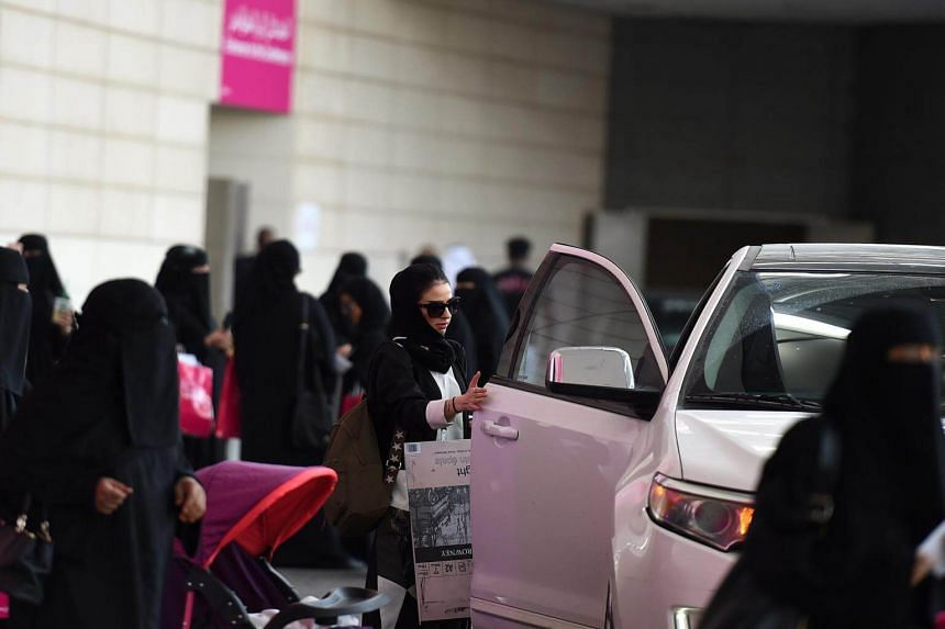 A Saudi woman gets out of her car as others wait for their drivers on Sept 28, 2017.  Saudi Arabia on Tuesday said it would allow driving permits for women under a royal decree to take effect in June.