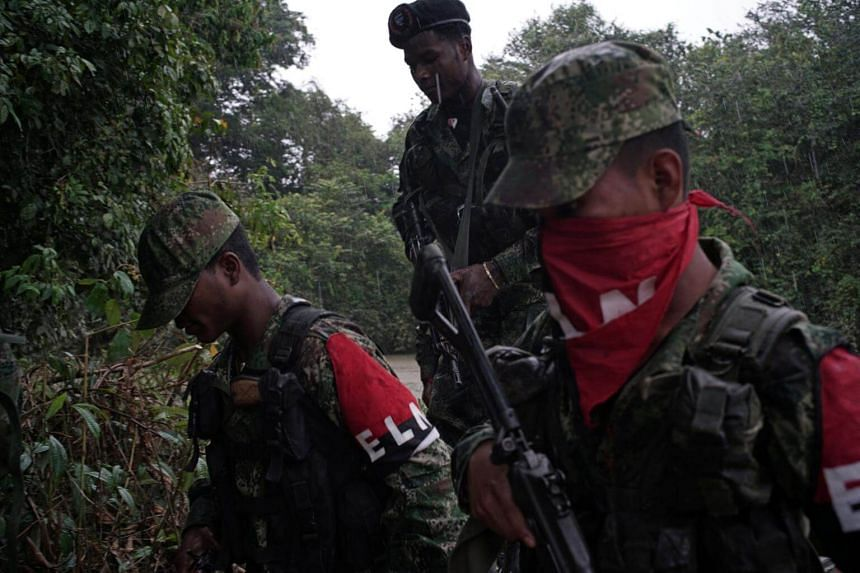 Rebels of Colombia's Marxist National Liberation Army (ELN) get off a boat after patrolling the river in the northwestern jungles of Colombia on Aug 30, 2017.  The initial ceasefire between the National Liberation Army rebels and government forces is