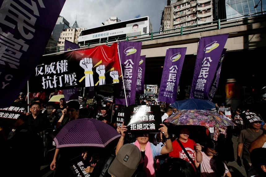 """Pro-democracy activists carry a banner reading """"anti-authority, against suppression"""" in Hong Kong on Oct 1, 2017. The protest also comes after recent arrests of prominent pro-democracy activists."""