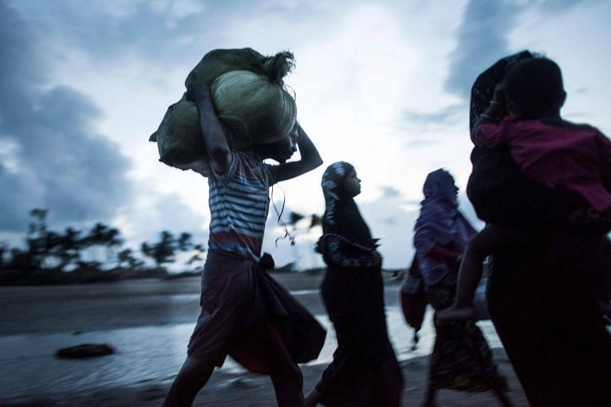 Rohingya Muslim refugees walking on the shore after crossing the border from Myanmar. A mob led by Buddhist monks attacked a centre housing Rohingya Muslims including children on the outskirts of Colombo last week.