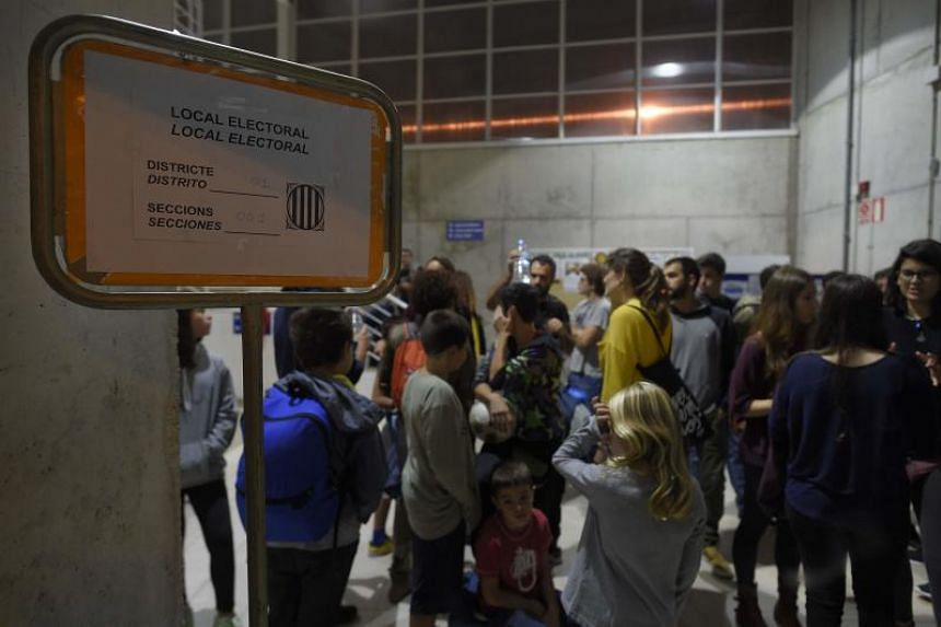 People gather at a would-be polling station, where Catalan president Carles puigdemont is expected to vote, in Barcelona, on Oct 1, 2017, to prevent the police to seal it off in a referendum on independence for Catalonia banned by Madrid.