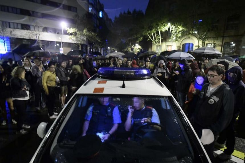 Catalan police sit in their patrol car as people gather outside a polling station in Barcelona, on Oct 1, 2017, to prevent the police to seal it off in a referendum on independence for Catalonia banned by Madrid.