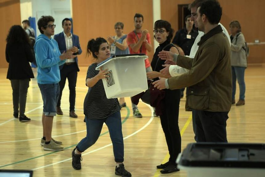 Volunteers carry ballot boxes in a polling station Sarria de Ter, where Catalan president will vote, on Oct 1, 2017, on the day of a referendum on independence for Catalonia banned by Madrid.