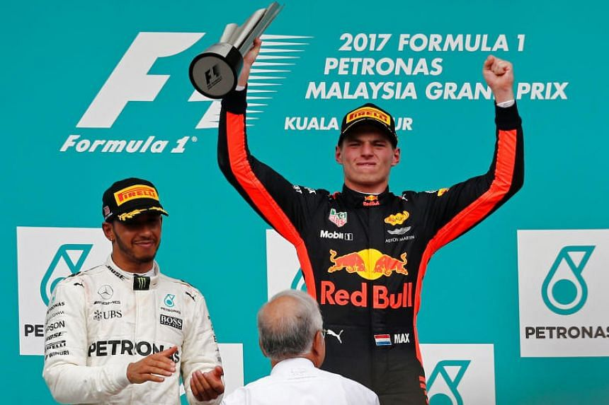 Redbull's Max Verstappen celebrating his victory at the last Malaysian Grand Prix alongside Mercedes' Lewis Hamilton and Malaysian Prime Minister Najib Razak.