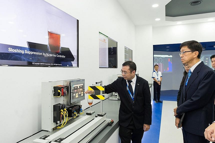 Professor Quek Tong Boon (right), CEO of the National Robotics Programme, at a product demonstration at Omron Automation Centre.