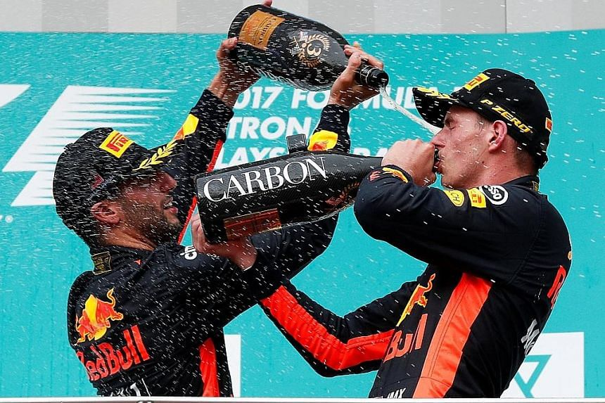 Red Bull team-mates Max Verstappen (right) and Daniel Ricciardo celebrate on the podium after their 1-3 finish.