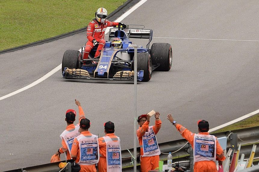 Ferrari's Sebastian Vettel is given a lift by Pascal Wehrlein of Sauber after he collided with Lance Stroll's Williams during the slow-down lap at Sepang.