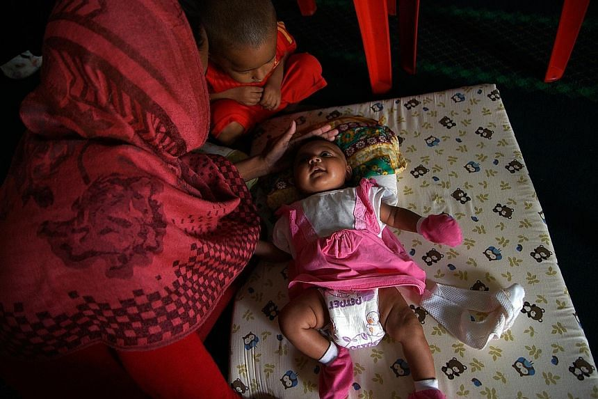 Ms Sawmira, 19, caressing her baby while a neighbour's child looks on. The Rohingya teenager was flown into Malaysia via Bangladesh last year using a fake passport, to marry a man she had never met. Malaysia's Prime Minister Najib Razak posing for pi