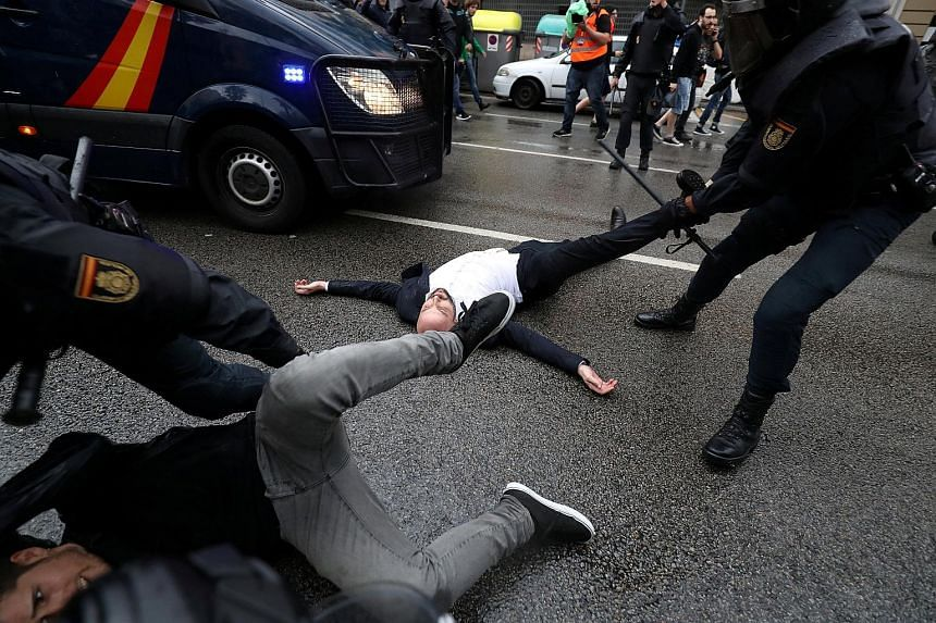Police officers removing demonstrators outside a polling station in Barcelona yesterday. The referendum on Catalonia's independence from Spain has been ruled unconstitutional by the central government and the courts.