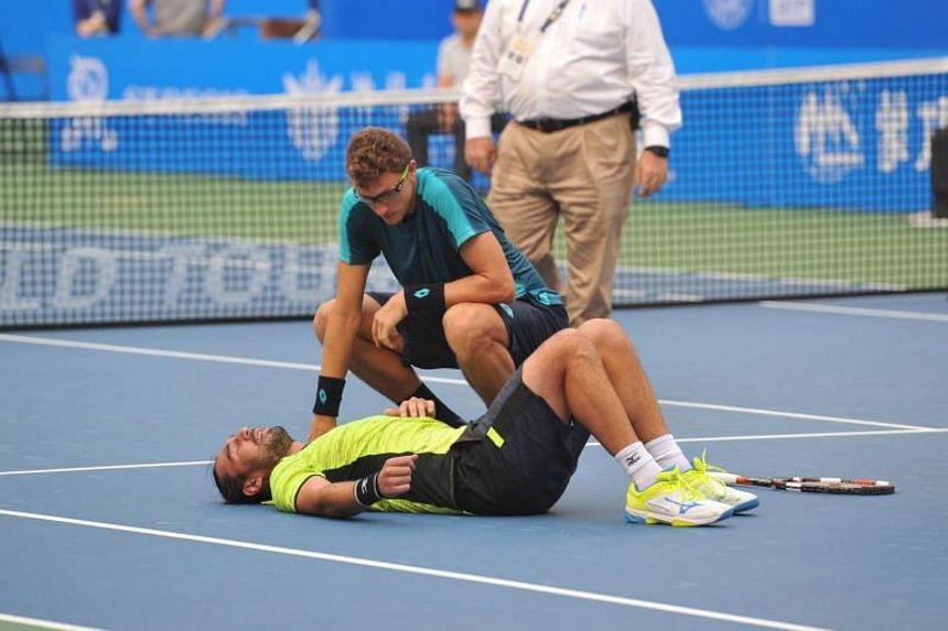 Uzbekistan's Denis Istomin (right) with injured Cyprus' Marcos Baghdatis during the ATP Chengdu Open tennis tournament in Chengdu, China on Oct 1, 2017.