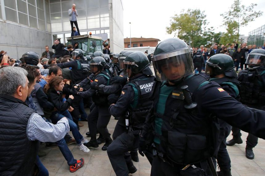 People clashing with Spanish Guardia Civil guards outside a polling station in Sant Julia de Ramis, on Oct 1, 2017.