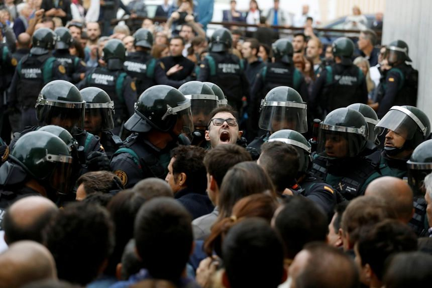 Scuffles break out as Spanish Civil Guard officers force their way through a crowd and into a polling station for the banned independence referendum, on Oct 1, 2017.