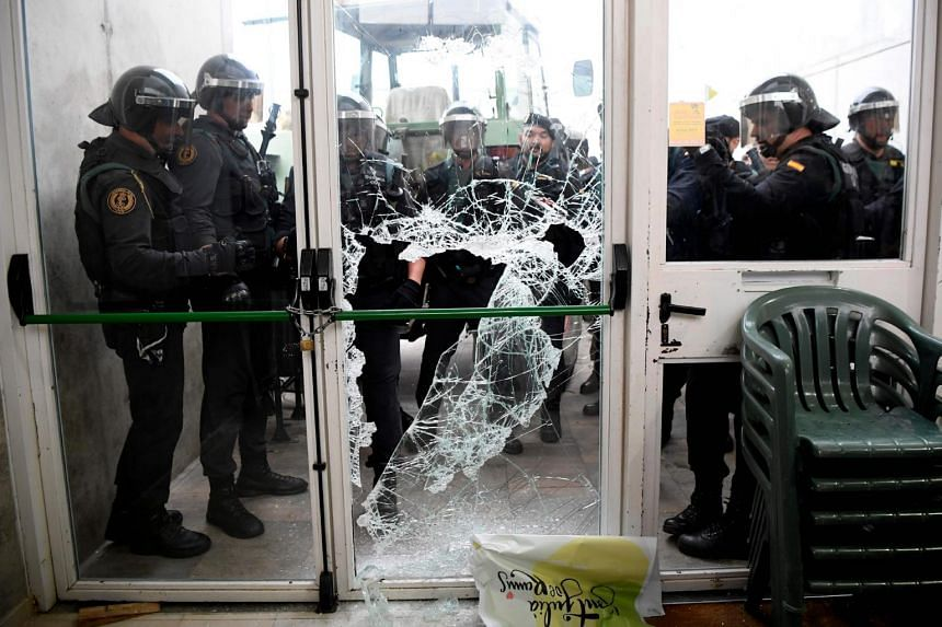 Spanish Guardia Civil guards breaking the door of a polling station in Sarria de Ter, where the Catalan president is supposed to vote, on Oct 1, 2017.