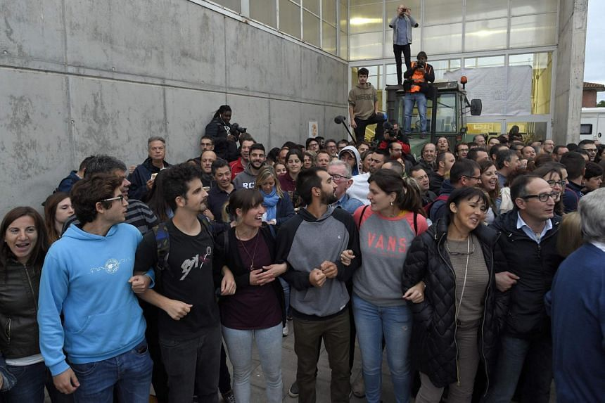 People gather waiting for the arrival of the police at the entrance of a polling station in Barcelona, on Oct 1, 2017.