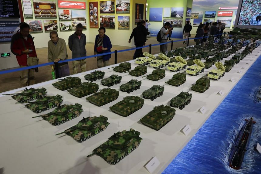 Visitors view models of Chinese military equipment during an exhibition showcasing China's achievements over the past five years at the Beijing Exhibition Hall in Beijing, China, on Sept 28, 2017.