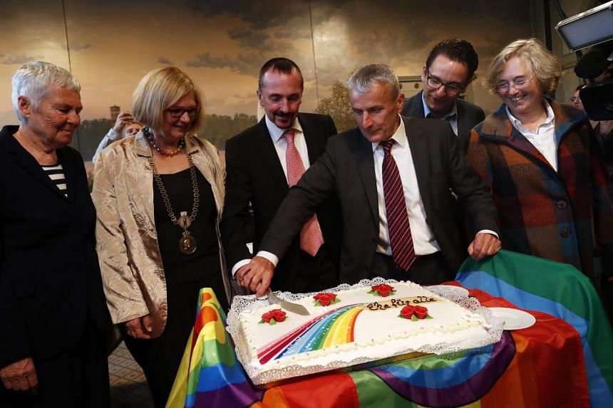 Mr Karl Kreile (third, left) and Mr Bodo Mende (third, right) cut the wedding cake between marriage witnesses during the first civil wedding ceremony between two men in Berlin, Germany, on Oct 1, 2017.