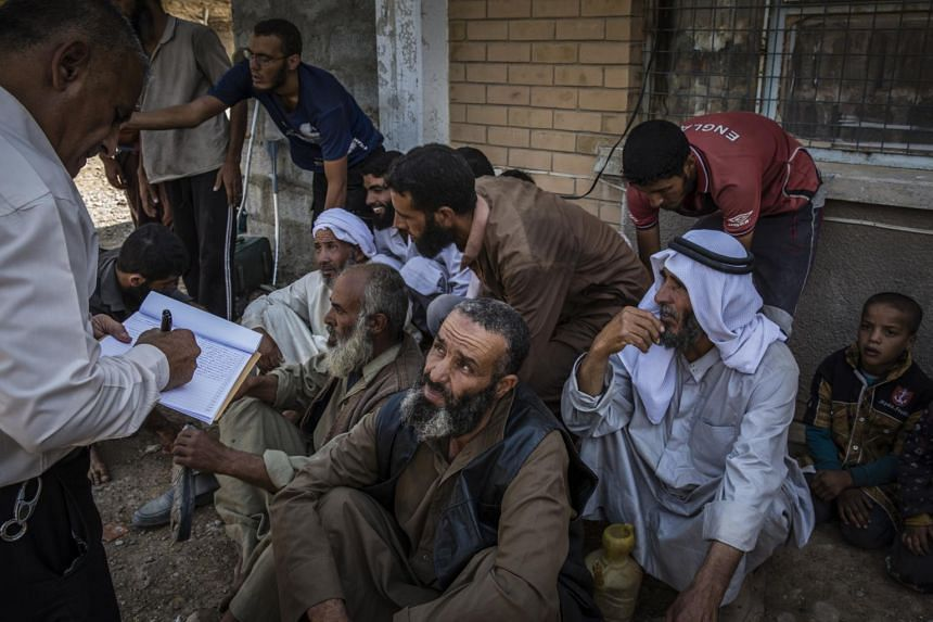 Displaced men suspected of being ISIS members are being questioned at a security screening center in Kirkuk, Iraq, on Oct 1, 2017.