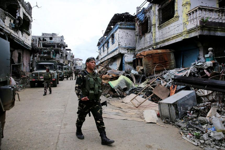 Government soldiers walk past damaged buildings and houses as troops continue their assault on clearing operations against the pro-IS militant group, which seized Mapandi district in Marawi city, on Sept 13, 2017.