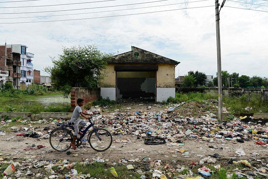 A boy rides a bicycle near a littered path in Gonda district, in the Indian state of Uttar Pradesh, on Aug 20, 2017.