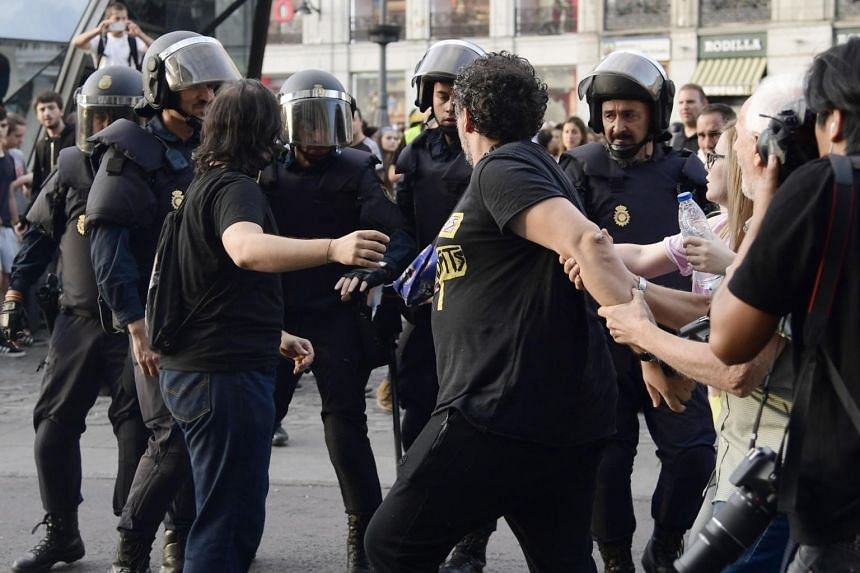 Some protesters confront Spanish National police officers during a demonstration at Puerta del Sol square in support of the right to hold a referendum on self-determination in Catalonia and against repression, in Madrid, on Oct 1, 2017.