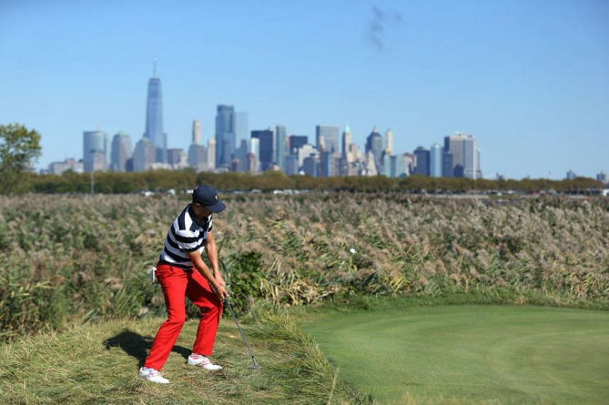 US golfer Justin Thomas hits a chip shot onto the tenth hole against the backdrop of New York city on the final day of the President's Cup golf tournament on Oct 1, 2017.