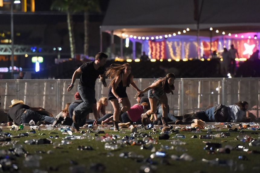 Concertgoers run for cover after a gunman opened fire at a music festival in Las Vegas on Oct 1, 2017.