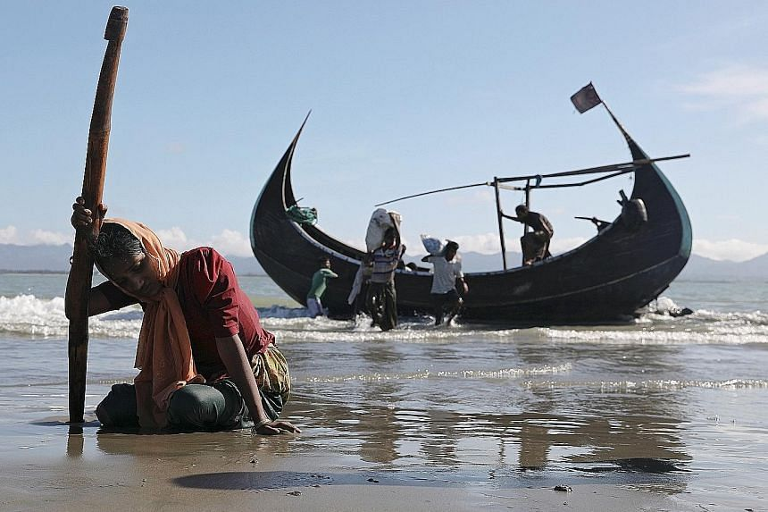 A refugee woman collapses from exhaustion after reaching the shores of Shah Porir Dwip, Bangladesh, on Sunday in a wooden boat from Myanmar.