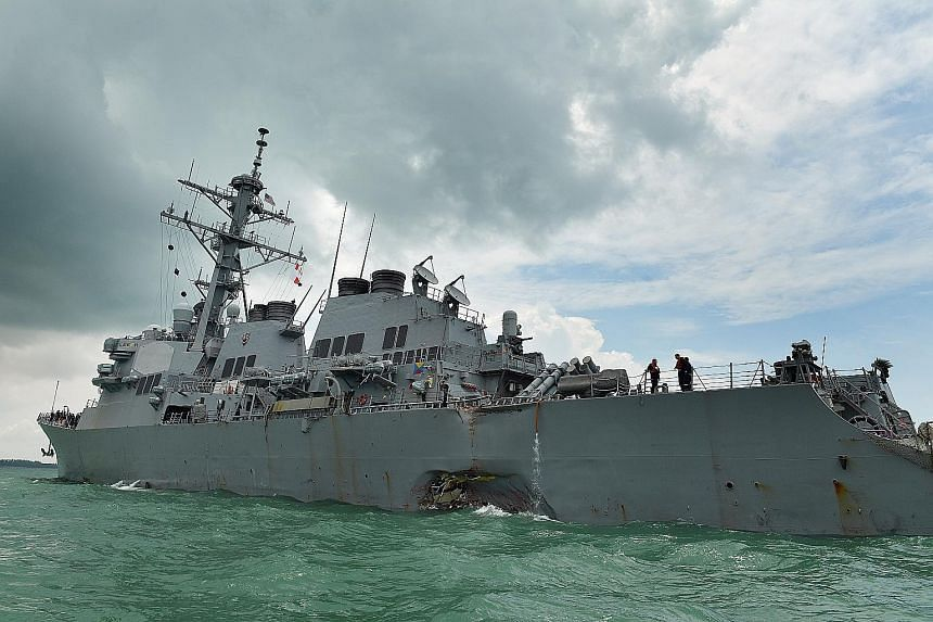 The damaged USS John S. McCain after its collision with a tanker on Aug 21. Under international regulations, the master and crew of the vessels are responsible for guiding the ships safely through, said Defence Minister Ng Eng Hen.