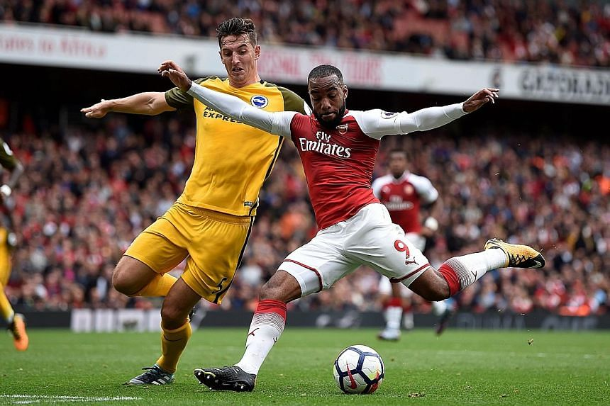 Arsenal striker Alexandre Lacazette holding off Brighton defender Lewis Dunk on Sunday. The French international has scored four goals in seven league matches, but Wenger feels he still needs more time to get up to speed.