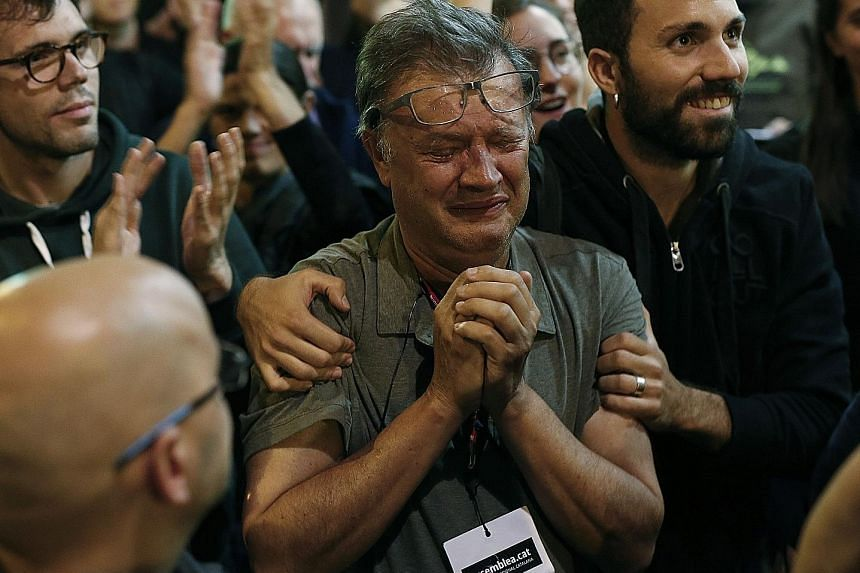 A Catalan National Assembly member getting emotional at the La Fontana youth centre polling station on Sunday in Barcelona. The referendum garnered 90 per cent support.