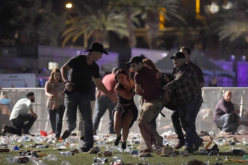 Concert-goers at the Las Vegas festival venue. The bursts of gunfire sent people running for their lives and sparked confusion. Far left: People carrying an injured person to safety after gunfire broke out at the Route 91 Harvest country music festiv