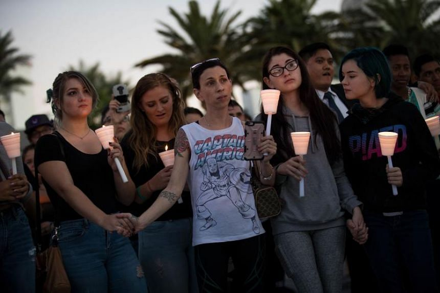 Mourners attend a candlelight vigil on Oct 2, 2017, at the corner of Sahara Avenue and Las Vegas Boulevard for victims of  the mass shooting.
