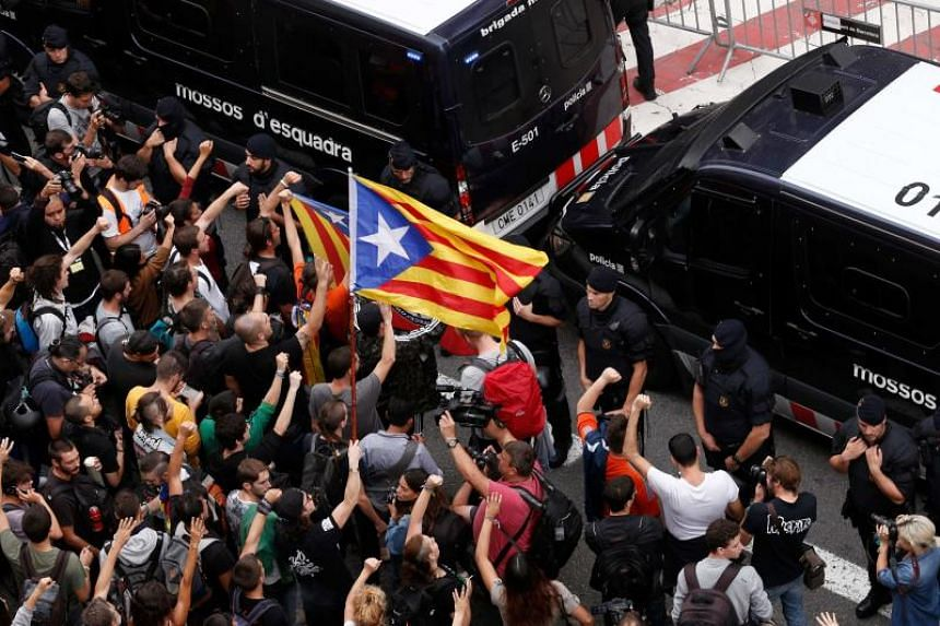 Protesters wave a Catalan pro-independence 'Estelada' flag during a demonstration outside the Spanish national police headquarters in Barcelona on Oct 2, 2017.