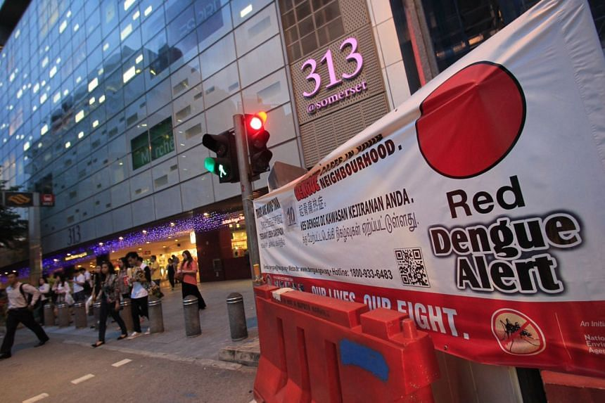 The exterior of 313 Somerset and a banner showing dengue alert.
