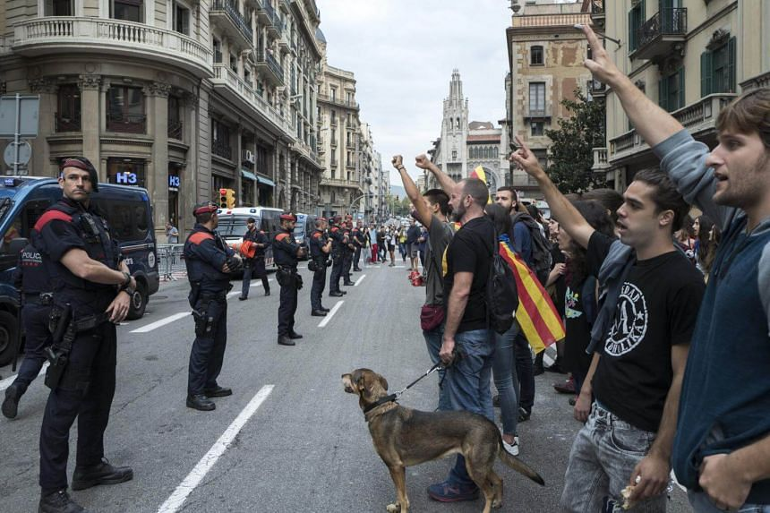 Catalonians blocking a Spanish police station in central Barcelona on Oct 3, 2017. A general strike was called for Tuesday after Spanish police forcibly tried to close polling stations on Sunday.