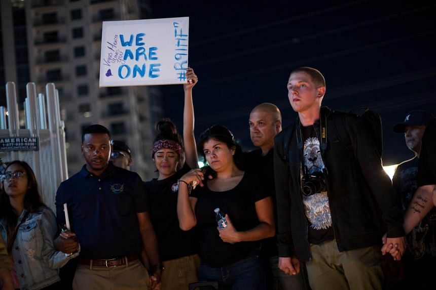 Mourners attend a candlelight vigil at the corner of Sahara Avenue and Las Vegas Boulevard for the victims of Sunday night's mass shooting on Oct 2, 2017.