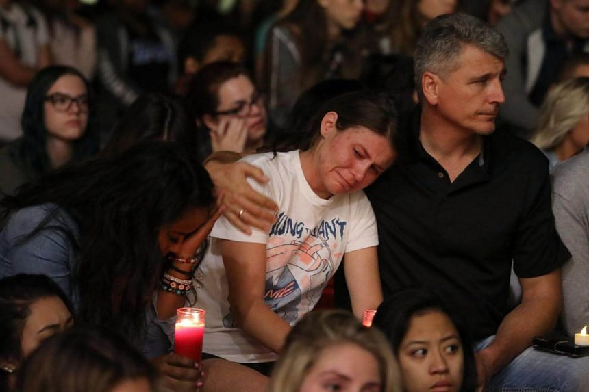 Mourners react during a candlelight vigil at the University of Nevada Las Vegas (UNLV) for victims of a mass shooting in Las Vegas, Nevada on USA, Oct 2, 2017.