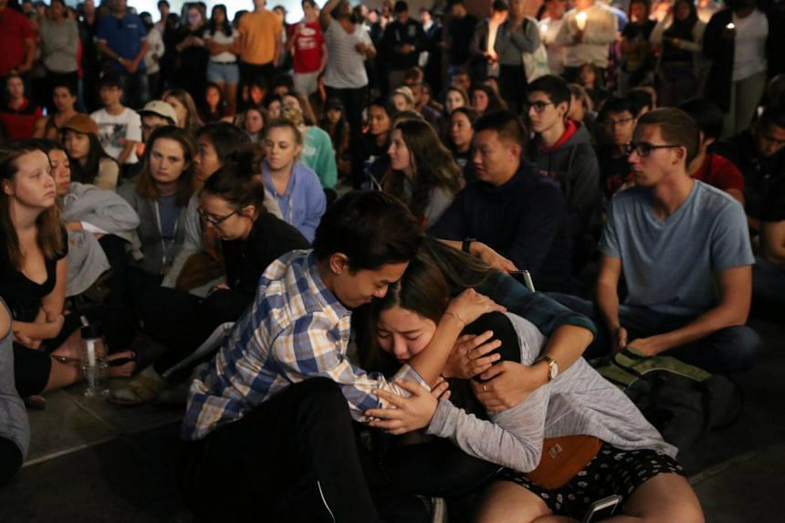 Student mourners console each other during a candlelight vigil at the University of Nevada Las Vegas (UNLV) for victims of a mass shooting in Las Vegas, Nevada on Oct 2, 2017.
