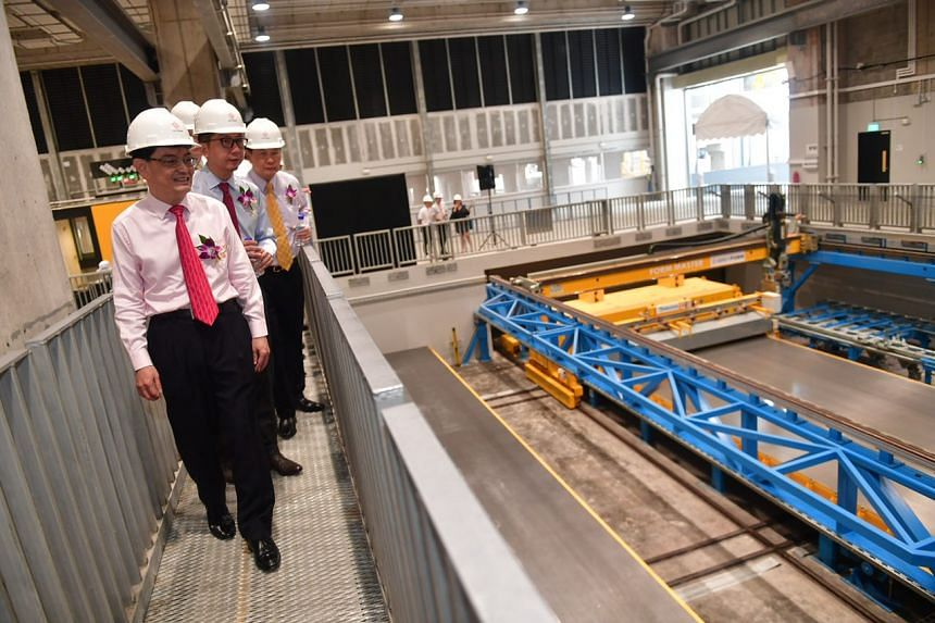 Minister of Finance Heng Swee Keat (left) and Group Managing Director and CEO for Straits Construction Group Wong Chee Herng (behind Mr Heng) viewing the Automated Pallet Circulation Plant.