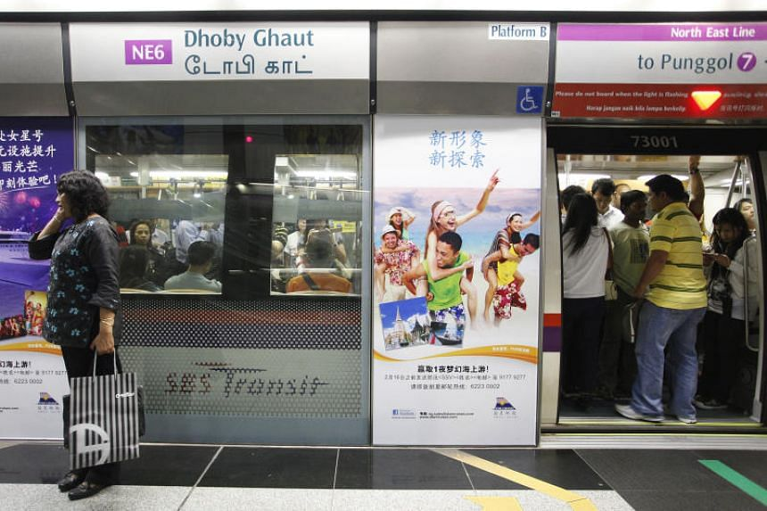 Commuters getting into a train at the Dhoby Ghaut MRT station on the North East Line.