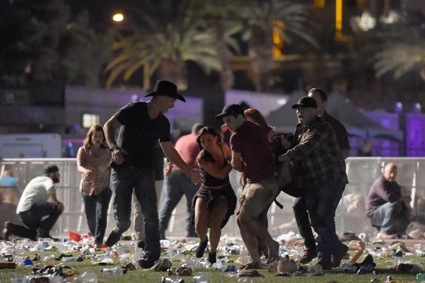 People carry a person at the Route 91 Harvest country music festival after apparent gun fire was heard.