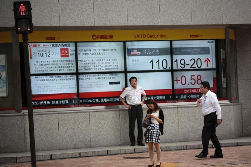 Pedestrians walk past a stock quotation board flashing the current foreign exchange rate of the yen against the US dollar in Tokyo.