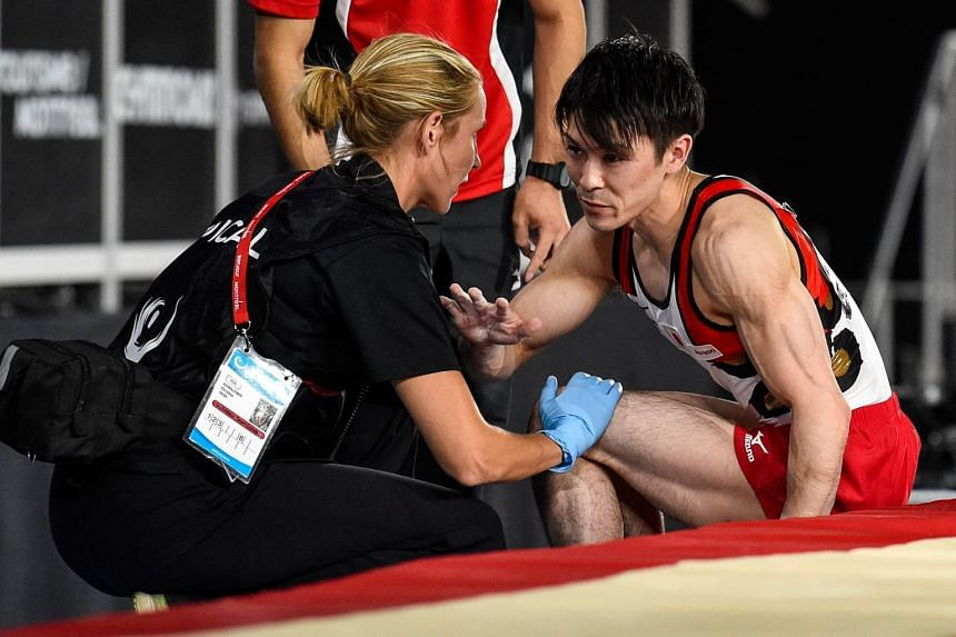 Kohei Uchimura of Japan is seen by medical staff after competing on the vault during day one of the Artistic Gymnastics World Championships.