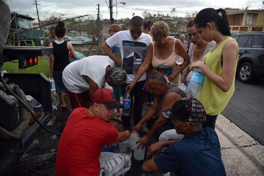 People take water from tanks in a truck in Juventud neighborhood, Puerto Rico.