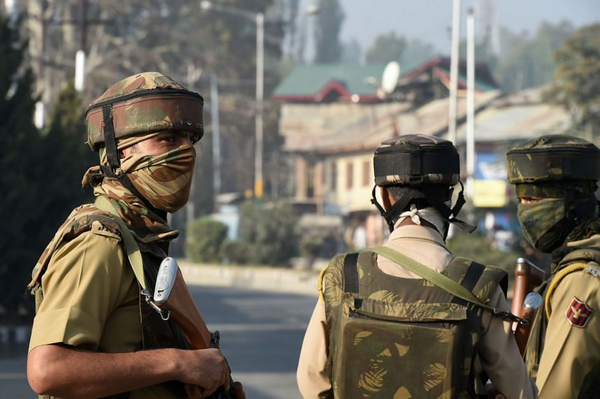 An Indian policeman stands guard near the site of gunfight between suspected militants and Indian government forces in Srinagar on Oct 3, 2017.