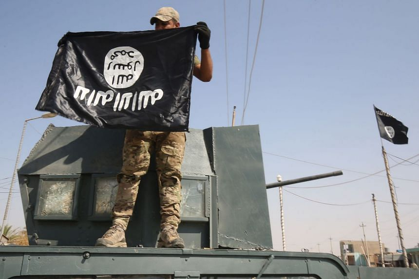 An Iraqi forces' fighter holds an upside-down ISIS flag on a humvee in Sharqat, Sept 22, 2017.
