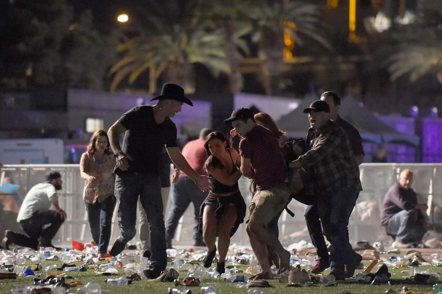 People carry a person at the Route 91 Harvest country music festival after apparent gun fire was heard in Las Vegas, Nevada, on Oct 1, 2017.
